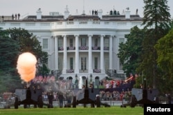 """Canons are shot as members of the military parachute onto the Ellipse of the White House during the """"Salute to America"""" event held to celebrate Fourth of July Independence Day in Washington, U.S., July 4, 2020. REUTERS/Sarah Silbiger"""