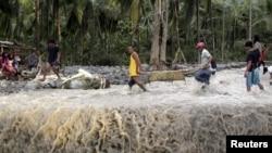 Warga mengangkat korban banjir bandang pasca hantaman topan Bopha di kota kecil New Bataan di Compostela Valley, Filipina (5/12).