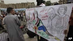 "An Egyptian protester carries a banner with drawings depicting ex president Mubarak and reads in Arabic ""No forgiveness, our children's blood is not cheap,"" during a protest at Tahrir Square in Cairo, Egypt, May 27, 2011."