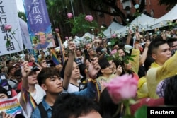 Same-sex marriage supporters hold roses to mourn those who committed suicide because of discrimination during a parliament vote on three draft bills of a same-sex marriage law, outside the Legislative Yuan in Taipei, Taiwan, May 17, 2019.