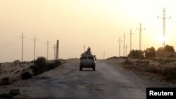 FILE - An Egyptian military vehicle is seen on a highway in northern Sinai, Egypt, May 25, 2015.