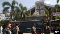 Cảnh sát Indonesia canh gác cạnh một chiếc xe bọc thép bên ngoài một nhà thờ ở Solo sau vụ nổ bom, ngày 25/9/2011