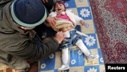 A doctor treats an internally displaced child in a school at a village outside Damascus, January 28, 2013.