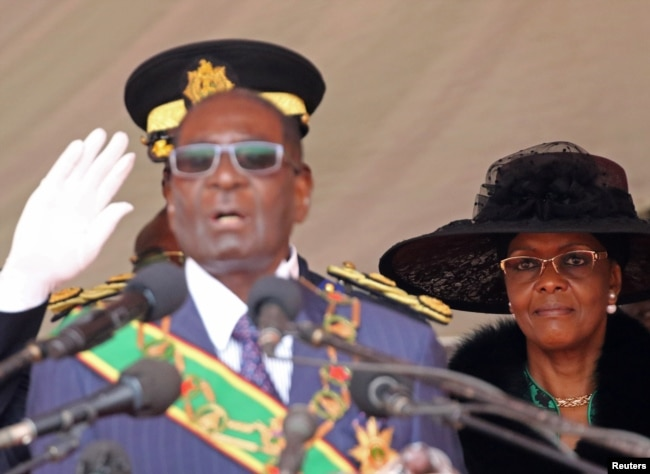 FILE - Zimbabwe President Robert Mugabe and his wife, Grace, look on during the Defense Force's 36th Anniversary celebrations in the capital Harare, Zimbabwe, Aug. 9, 2016.