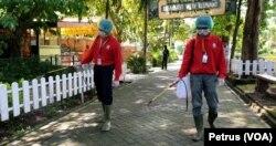 Petugas melakukan penyemprotan desinfektan di jalanan di bagian dalam Kebun Binatang Surabaya sebagai langkah pencegahan penyebaran virus corona (foto Petrus Riski-VOA)