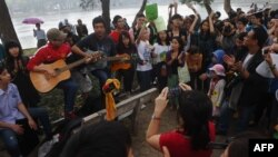 FILE - People sing during a rally protesting against a tree-felling plan by the municipal authorities in Hanoi, March 22, 2015.
