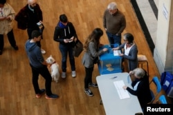 People line up to cast their ballots in the first round of 2017 French presidential election at a polling station in Lyon, France, April 23, 2017.