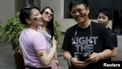 FILE – A 2015 Pride Run in Shanghai celebrates lesbian, gay, bisexual and transgendered people. But most LGBT Chinese hide their sexual orientation, fearing discrimination, a new UN report finds.