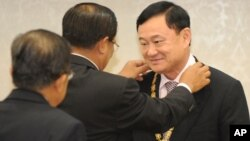 Former Thai Prime Minister Thaksin Shinawatra, right, receives a medal from Cambodia's Prime Minister Hun Sen, center, during the Medal Decoration ceremony at Cambodia Peace Palace in Phnom Penh, Monday, Sept. 19, 2011.