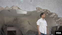 Seorang pria berdiri di muka komplek tempat tinggal Gaddafi di Tripoli yang rusak berat akibat serangan NATO yang menewaskan putera dan tiga cucu Gaddafi.