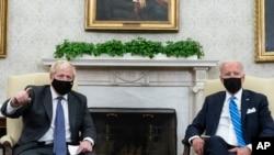 FILE - President Joe Biden, right, listens as British Prime Minister Boris Johnson speaks during a meeting in the Oval Office of the White House, Sept. 21, 2021.