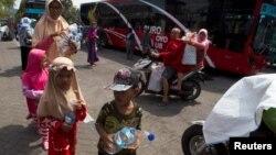 Warga Surabaya, termasuk anak-anak, membawa botol plastik bekas untuk ditukarkan dengan tiket Suroboyo bus di Terminal Purbaya (REUTERS/Sigit Pamungkas).