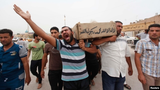 Relatives carry the coffin of an Iraqi police officer killed by militants during a funeral in Najaf, May 20, 2013.
