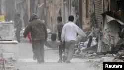 Dân chúng khiêng một người bị thương vì đạn pháo ở Homs