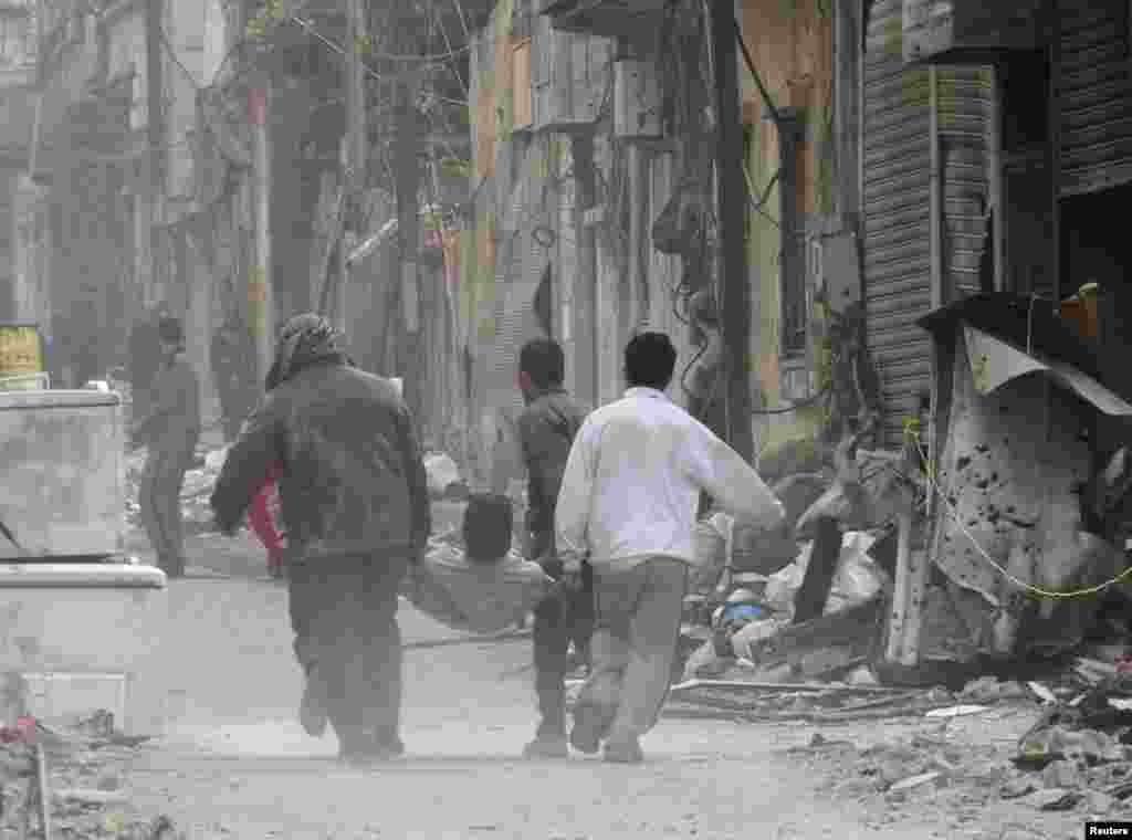 People carry a man on a stretcher after he was injured by shelling in the besieged area of Homs, Nov. 25, 2013.