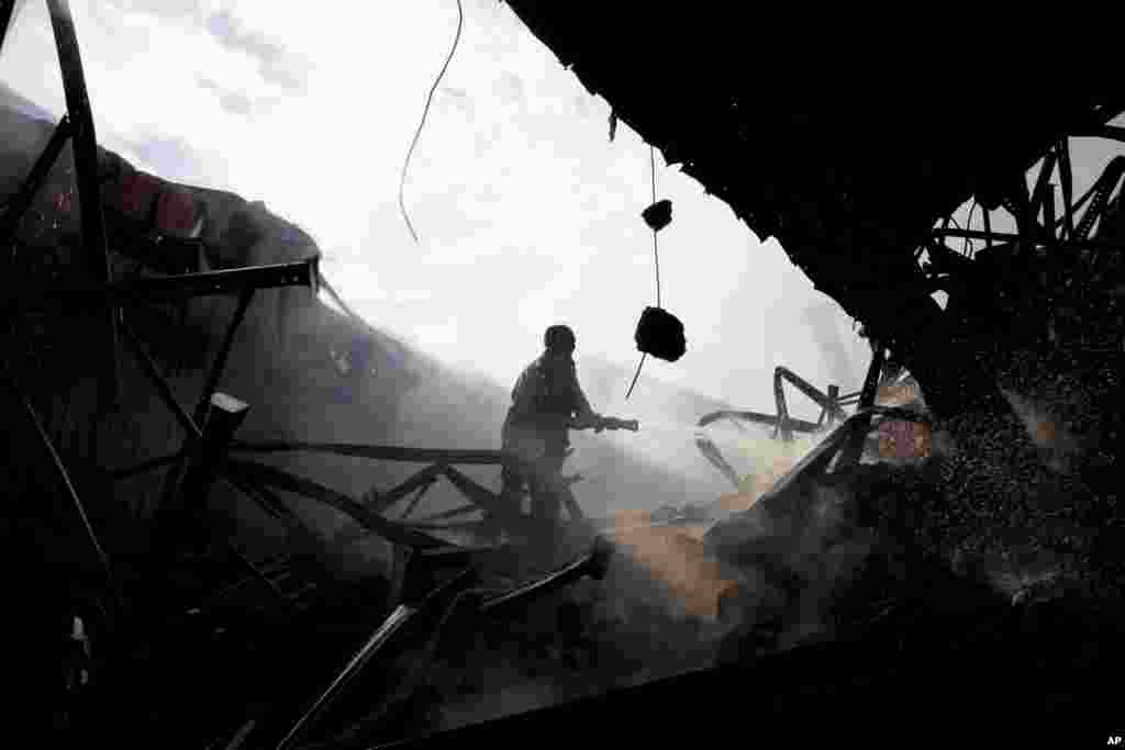 A firefighter tries to douse a fire at a garment factory in Gazipur outside Dhaka, Oct. 9, 2013.