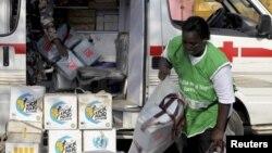 Nhân viên y tế khiêng dụng cụ tiêm chủng lên xe tại một trung tâm phân phối ở Lagos.