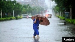 A worker holding an umbrella crosses a flooded street brought about by heavy rain from Typhoon Soulik in Quanzhou, Fujian province, July 13, 2013.