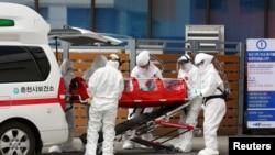 一位確診感染冠狀病毒的病人在南韓春川被推進一家醫院(2020年2月20日)。