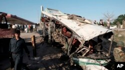 Pasukan keamanan Afghanistan memeriksa bus yang hancur pasca serangan bunuh diri di Jalalabad, Afghanistan, Senin (11/4).