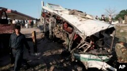 Afghans and security forces inspect damage to a bus after a suicide attack in Jalalabad east of Kabul, April 11, 2016.