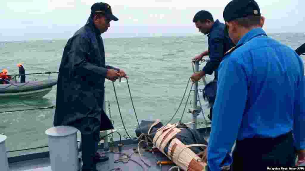 Elementos da Marinha Naval Real Malaia retiram uma vítima do Mar de Java. O avião da Air Asia caiu a 28 de Dezembro. Indonésia Dez. 31, 2014.