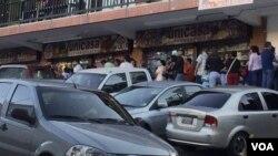 Filas de clientes aguardan en las afueras de un establecimiento comercial de Caracas para comprar productos básicos. El gobierno niega la escasez.
