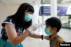 Seorang guru memeriksa suhu tubuh seorang murid di sebuah sekolah di Tangerang, 6 Maret 2020. (Foto: Reuters)