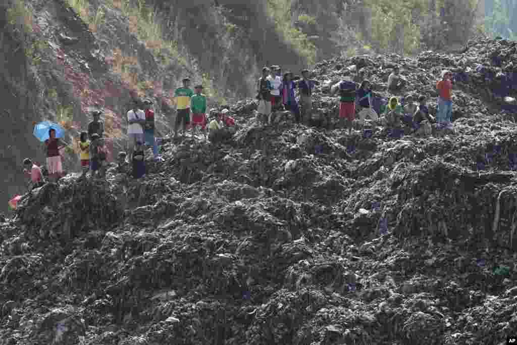 Công nhân và cư dân đứng trên một núi rác tại một bãi rác trong một vụ cứu nạn tại San Isidro, tỉnh Rizal, phía đông Manila, Philippines. Cảnh sát cho biết 4 công nhân được ghi nhận mất tích sau khi một bãi rác chuồi dọc theo một sườn núi.