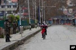មនុស្សម្នាក់ជិះកង់កាត់ទាហានប៉ារ៉ាឥណ្ដា នៅពេលពួកគេឈរយាមនៅលើផ្លូវស្ងាត់ច្រងំមួយនៅពេលបិទប្រទេសក្នុងក្រុង Srinagar កាលពីថ្ងៃទី២៥ ខែមីនា ឆ្នាំ២០២០។