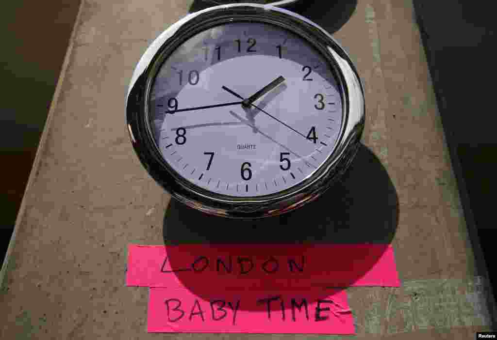 A clock, July 15, 2013, in the press pen shows the time outside the Lindo Wing of St. Mary's Hospital, where Britain's Catherine, Duchess of Cambridge, is due to give birth, in London.