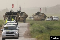 Kurdish fighters from the People's Protection Units (YPG) head a convoy of U.S military vehicles in the town of Darbasiya next to the Turkish border, Syria, April 28, 2017.