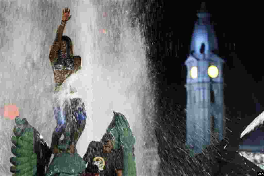 People play in the Swann Memorial Fountain, at Logan Square, in view of City Hall, right, after an Independence Day celebration Monday, July 4, 2011, in Philadelphia. The U.S. celebrated the 235th anniversary of the signing of the Declaration of Independe