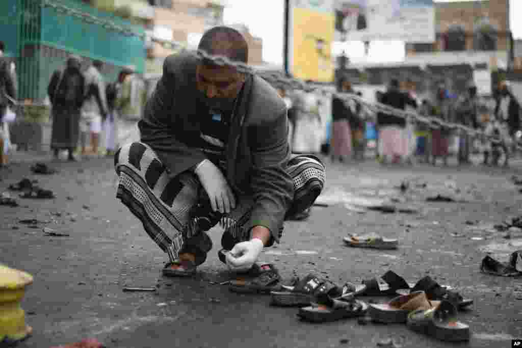 A Yemeni security official inspects objects near the site of a suicide bombing in Sana'a, Oct. 9, 2014.