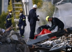 FILE - Emergency workers search through rubble at the site of the CTV building in Christchurch, New Zealand, Feb. 24, 2011, after the city was hit by an earthquake Tuesday.