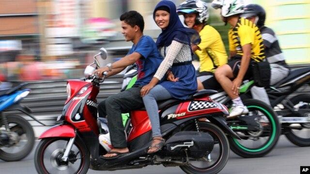 Một phụ nữ ngồi (dạng chân) trên xe gắn máy chạy trên một con đường trong tỉnh Aceh, Indonesia