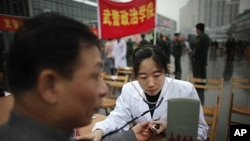 """A member of the Chinese military forces gives a free medical check to a man as community service during the """"Learning from Lei Feng Day"""" in a central square in Shanghai, March 5, 2012."""