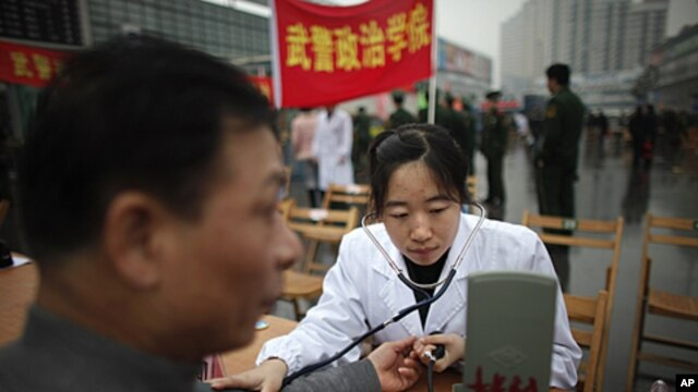 "A member of the Chinese military forces gives a free medical check to a man as community service during the ""Learning from Lei Feng Day"" in a central square in Shanghai, March 5, 2012."