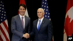Canadian Prime Minister Justin Trudeau and Vice President Mike Pence shake hands at the start of a bilateral meeting at the second day of the National Governors Association meeting, July 14, 2017, in Providence, Rhode Island.