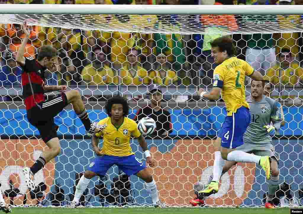 Germany's Thomas Mueller (L) scores the team's first goal next to Brazil's David Luiz (4) as Marcelo (6) and Brazil goalkeeper Julio Cesar (12) watch during the 2014 World Cup semi-finals at Mineirao stadium in Belo Horizonte, Brazil, July 8, 2014.