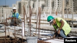 FILE - Palestinian laborers work at a construction site in Rawabi, near the West Bank city of Ramallah, Oct. 27, 2013.