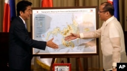 Japanese Prime Minister Shinzo Abe, left, and Philippine President Benigno Aquino III shake hands after Abe presented him with a topographical map of the country's third largest island of Mindanao, July 27, 2013.