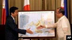 PM Jepang Shinzo Abe (kiri) dan Presiden Filipina Benigno Aquino berjabat tangan dalam pertemuan di Manila, Filipina (27/7).