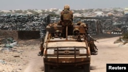 Kenya Defence Force (KDF) soldiers, serving in African Union Mission in Somalia (AMISOM), patrol past stockpiles of charcoal near the Kismayo sea port town (2013 photo)
