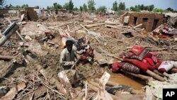 پاکستان میں مقیم ایک افغان مہاجر، سیلاب کی وجہ سے، اپنے تباہ شدہ گھر کے سامنے بیٹھا ہوا ہے