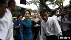 Pemimpin pro-demokrasi Myanmar Aung San Suu Kyi dan Utusan Khusus PBB urusan Pengungsi (UNHCR) Angelina Jolie Pitt tiba di hostel tempat tinggal para buruh perempuan di Kawasan Industri Hlaingtaryar, Yangon (1/8). (Reuters/Soe Zeya Tun)