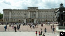 FILE - People are seen in front of Britain's Queen Elizabeth II's official London residence, Buckingham Palace, in London.