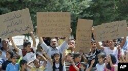 ژمارهیهک ئاوارهی سوریا له ئۆردوگایهک له تورکیا دروشمیان له دژی بهشـار ئهلئهسهد و دهسهڵاتهکهی بهرزکردۆتهوه و لهسهر دروشمێـکیان نووسراوه داوای ئازادیمان کرد ئاواره بووین، ههینی 10 ی شهشی 2011
