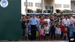 Ethnic Montagnards look from behind the gates of their temporary UNHCR (United Nations High Commission for Refugees) and IOM (International Organization for Migration) administered quarters in Phnom Penh, file photo.
