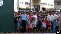 ជនភៀសខ្លួនពីតំបន់ខ្ពង់រាបវៀតណាម ឈរមើលពីខាងក្នុងរបងនៃជំរំស្នាក់នៅបណ្តោះអាសន្នដែលគ្រប់គ្រងដោយឧត្តមស្នងការអង្គការសហប្រជាជាតិសម្រាប់ជនភៀសខ្លួន(UNHCR) និងអង្គការអន្តោប្រវេសន៍អន្តរជាតិ (IOM)។